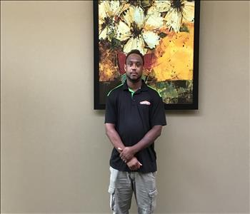 The male employee is attired in the SERVPRO uniform and artwork is in the background