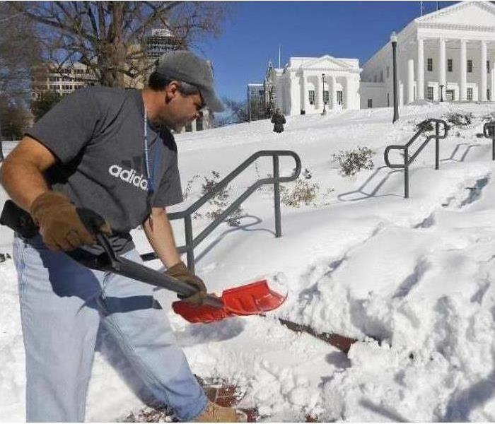 The worker used a shovel to remove several inches of snow that covered a huge area that goes to the White House.