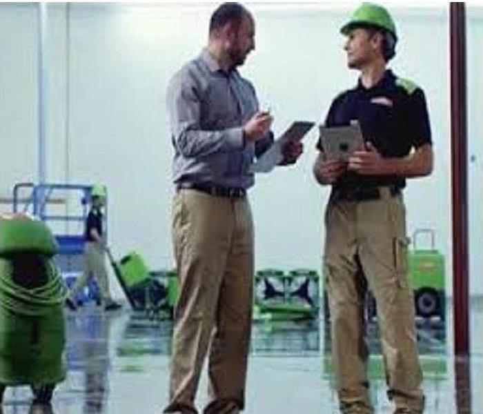 SERVPRO® Production Manager reviews the Scope of Work for a commercial water loss with the Owner of the property.