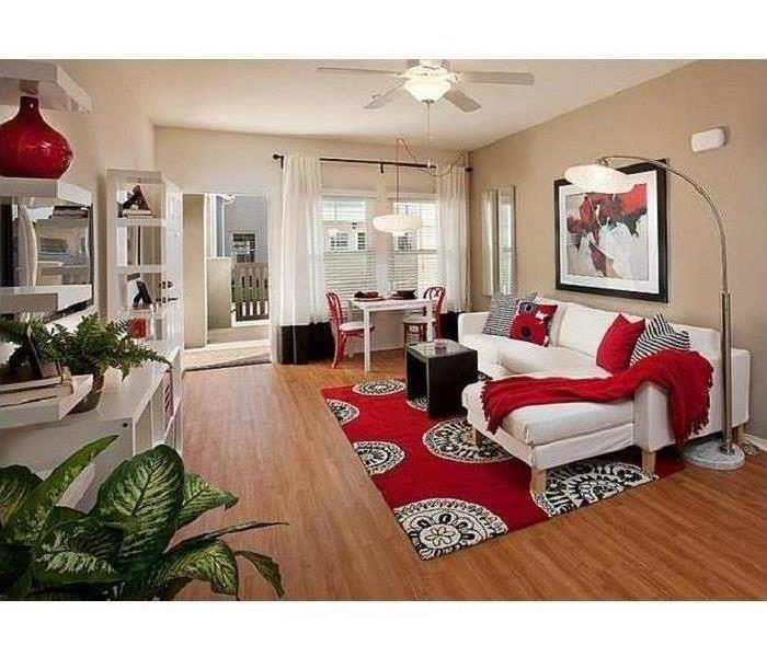 The room has neutral colors everywhere and accent colors of red, black, and white are accessories to blend with the furniture