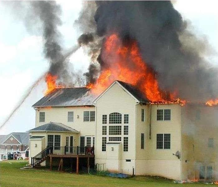 Fire engulfed the top of a house and causes severe fire damages while the smoke residue goes up the sky.